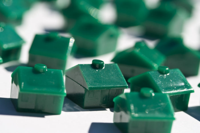 Multiple green monopoly houses on a white table