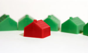 red monopoly house in front of four green monopoly houses