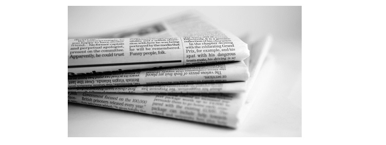 Four copies of a newspaper with a newsletter for tax accountants folded and stacked to the left of the photo