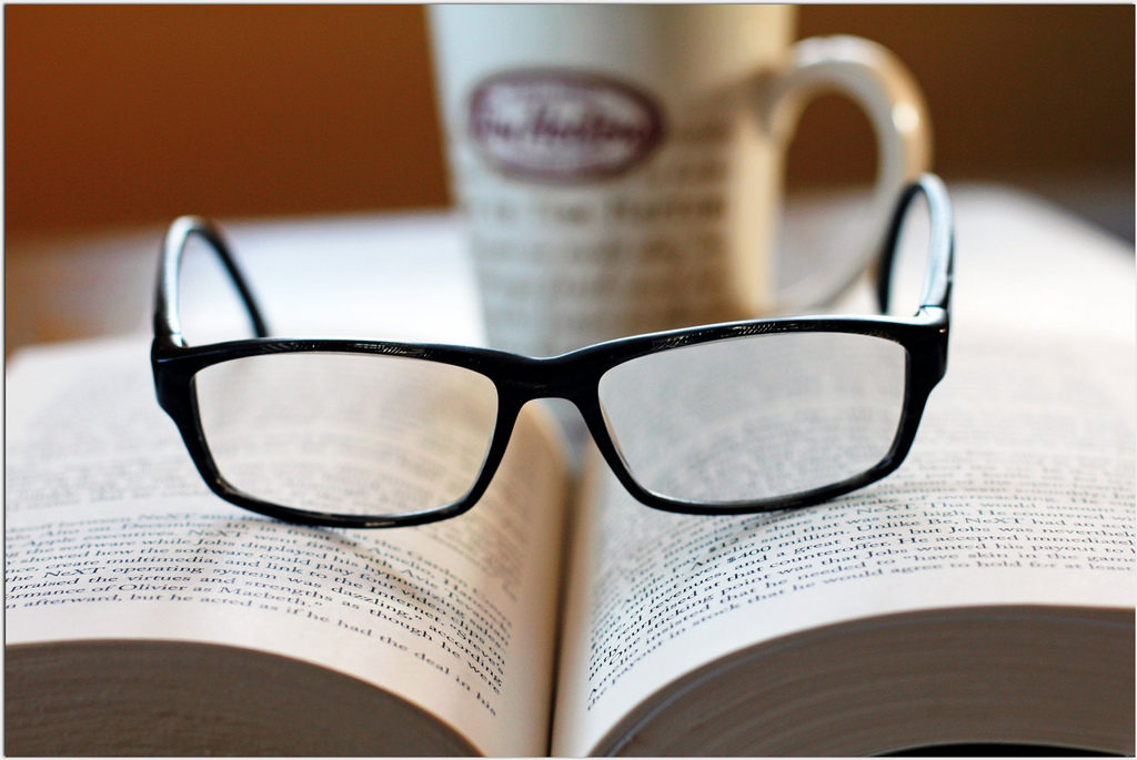 black reading glasses on an open book with a coffee cup behind it