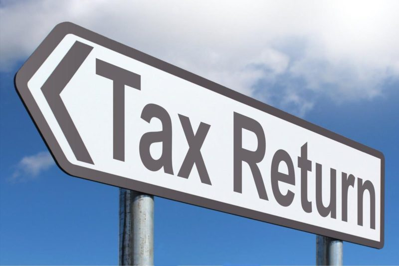 Photo of a Street Sign that says Tax Return Against A Background of a blue sky with clouds