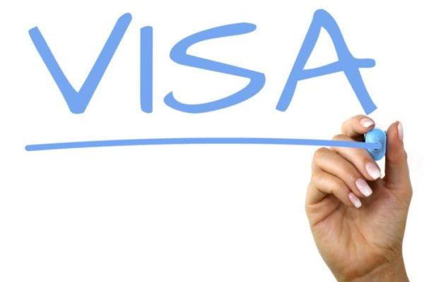Hand using marker to write visa on glass that says visa for eb-5 visa and investors