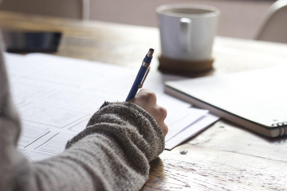 Girl In grey Sweater Doing Business Taxes At Wood Desk
